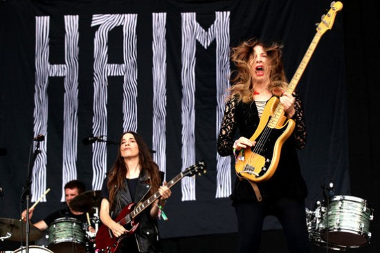 Ester Haim in the foreground playing @ Glastonbury 2013