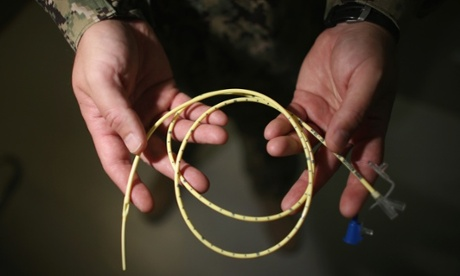 A military doctor holds a feeding tube used to feed detainees on hunger strike at Guantánamo. Photograph: Joe Raedle/Getty Images