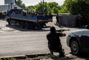 An anti-government fighter takes position behind a car as a truck full of self-defense forces heads towards the battle during clashes against Ukrainian forces near the airport in Donetsk on May 26, 2014. (AFP Photo / Fabio Bucciarelli)