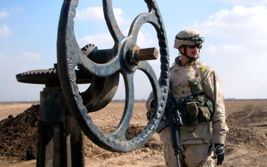 A U.S. soldier stands next to an oil pipeline valve in Iraq in 2005. (Photo: YourLocalDave/cc/flickr)