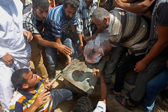 Palestinian relatives bury one of several children from the al-Najjar (Najar) family, killed in an Israeli air strike on their house in Khan Yunis, in the southern Gaza Strip, on July 26, 2014. (AFP Photo / Said Khatib)