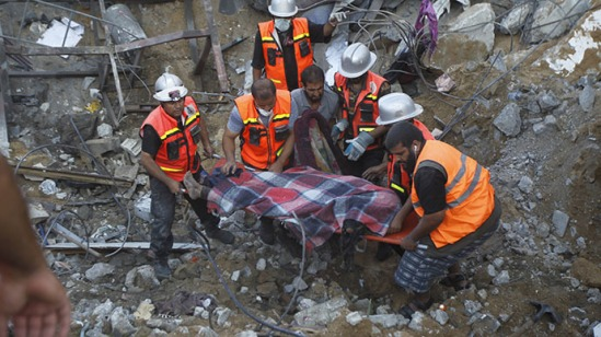 Rescue workers carry the body of a member of al-Najar family, after removing it from under the rubble of their home following an Israeli air strike on Khan Yunis in the southern of Gaza strip, on July 26, 2014. (AFP Photo / Said Khatib)