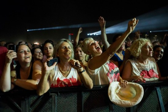Rolling Stones fans cheers as the band perform on stage.