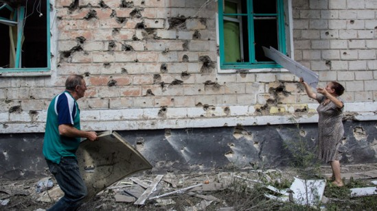Local residents near a residential building hit by a shell during the combat operations in the town of Shakhtyorsk near Donetsk.(RIA Novosti / Andrey Stenin)