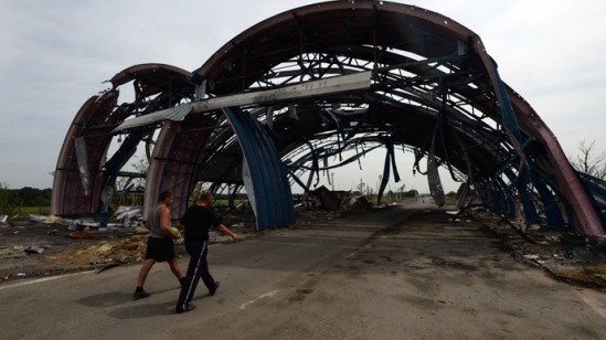 """Men near the destroyed checkpoint """"Dolzhansky"""" in Lugansk region.(RIA Novosti / Mikhail Voskresenskiy)"""