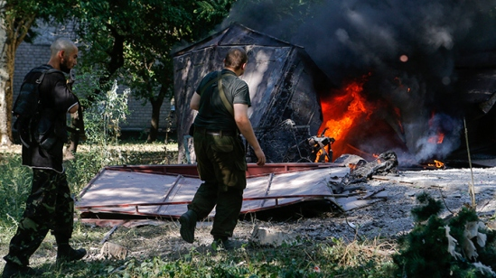 Armed anti-goverment fighters walk in front of garages set ablaze by what locals say was recent shelling by Ukrainian forces in Donetsk August 23, 2014 (Reuters / Maxim Shemetov)