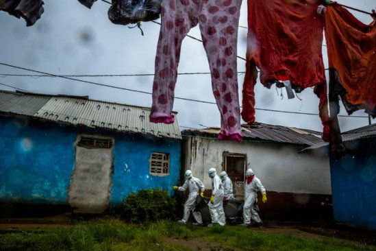 A Red Cross team removed the body of a woman believed to have died of Ebola in Monrovia, Liberia, last week. Officials urge caution in handling victims' bodies. Credit Daniel Berehulak for The New York Times