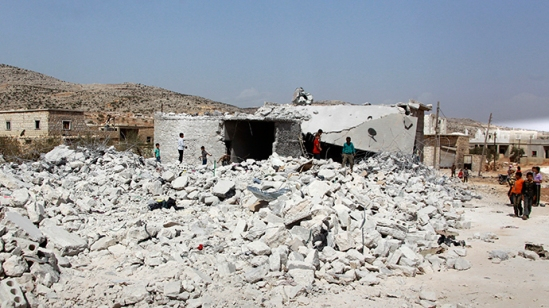 Residents look at buildings which were damaged in what activists say was one of Tuesday's U.S. air strikes in Kfredrian, Idlib province September 24, 2014 (Reuters / Ammar Abdullah)