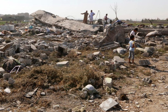 People view the debris of their homes after a Syrian war plane crashed in Raqqa, in northeast Syria September 16, 2014. (Reuters/Stringer)