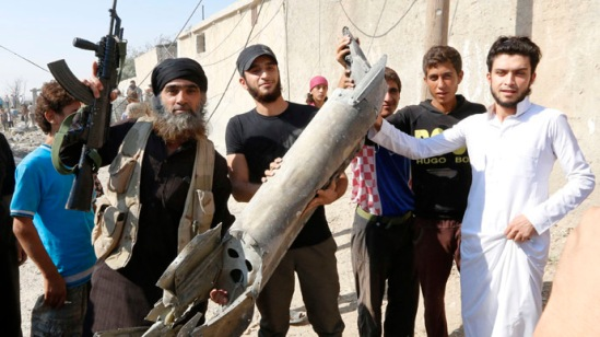 An Islamic State militant (L) stands next to residents as they hold pieces of wreckage from a Syrian war plane after it crashed in Raqqa, in northeast Syria September 16, 2014. (Reuters/Stringer)