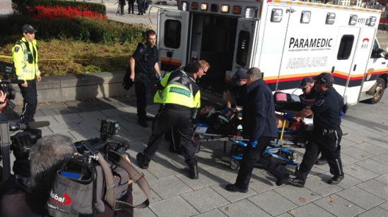This October 22, 2014 photo shows police and medical personell moving a wounded person into an ambulance at the scene of a shooting at the National War Memorial in Ottawa, Canada. (AFP Photo/Michel Comte)