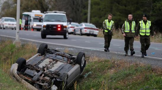 A Surete du Quebec (SQ) officer investigates an overturned vehicle in Saint-Jean-sur-Richelieu, Quebec October 20, 2014.(Reuters / Christinne Muschi)