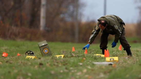 A Surete du Quebec (SQ) officer investigates the scene of a police shooting in Saint-Jean-sur-Richelieu, Quebec October 20, 2014.(Reuters / Christinne Muschi)