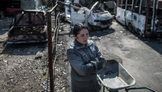 A woman stands in an area that was recently shelled in Donetsk, eastern Ukraine, September 16, 2014.