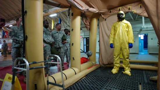 A soldier goes through the decontamination process with U.S. Army soldiers from the 101st Airborne Division (Air Assault), who are earmarked for the fight against Ebola, take part in training before their deployment to West Africa, at Fort Campbell, Kentucky (Reuters / Harrison McClary)