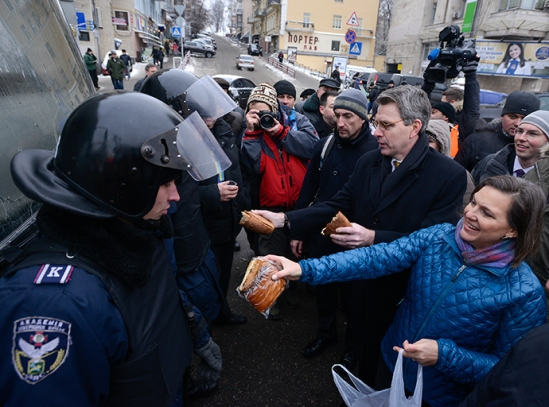 U.S. Assistant Secretary of State for European and Eurasian Affairs Victoria Nuland (R) and U.S. Ambassador Geoffrey Pyatt (2nd R) distribute bread to riot police near Independence square in Kiev December 11, 2013 (Reuters / Andrew Kravchenko)