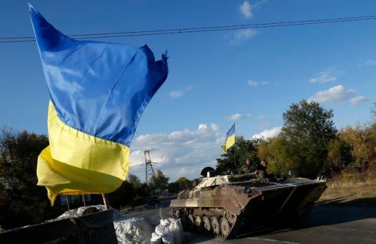 Ukrainian servicemen drive an armoured vehicle on the road near the eastern Ukrainian town of Horlivka, October 1, 2014. (Reuters/David Mdzinarishvili)