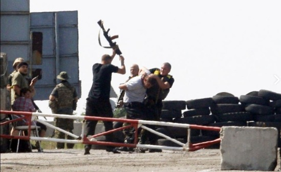 """Ukrainian soldiers detain a man, center, """"suspected"""" of spying for pro-Russian militants at a checkpoint near Debaltseve, in Ukraine's Donetsk region. Ukraine's crisis entered dangerous new territory with Kiev claiming its forces destroyed a Russian military convoy, while the United States warned Moscow over its """"provocative"""" efforts at destabilisation. Anatolii Stepanov/AFP via Getty Images"""
