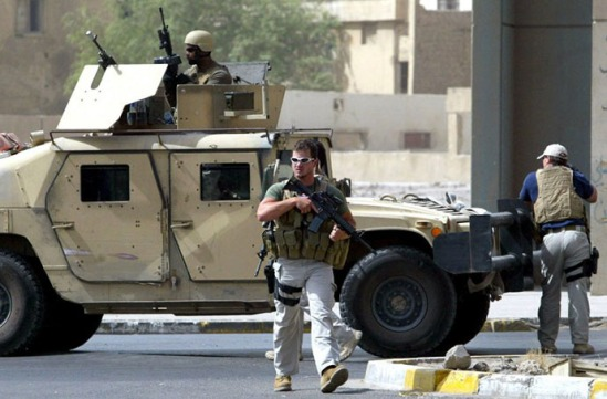 (FILES) A picture taken on July 5, 2005 shows contractors of the US private security firm Blackwater securing the site of a roadside bomb attack near the Iranian embassy in central Baghdad. (AFP Photo / Ahmad Al-Rubaye)