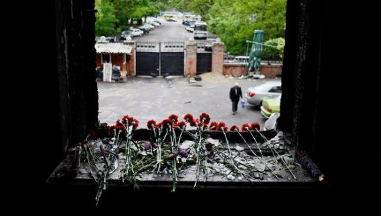 Flowers on a broken window in memory of the people killed by fire in the Trade Unions House on Odessa's Kulikovo Field Square