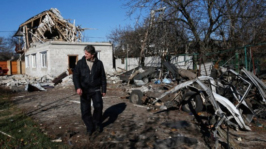 A man walks past a residential block and a car damaged by recent shelling in Donetsk, eastern Ukraine.(Reuters / Maxim Zmeyev)