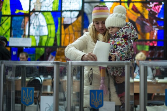 A woman puts a ballot into a ballot box at a polling station in Kiev during the Ukrainian early parliamentary election. (RIA Novosti/Ramil Sitdikov)