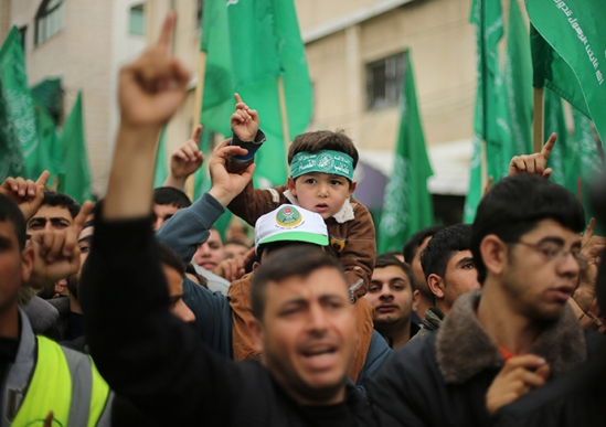 A Palestinian boy wearing the headband of Hamas's armed wing sits on the shoulders of his father during a rally ahead of the 27th anniversary of Hamas founding, in Jabaliya in the northern Gaza Strip December 12, 2014 (Reuters / Mohammed Salem)