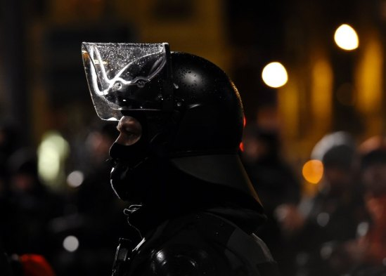 Police officers in riot gear watch protestors from the PEGIDA movement (Patriotic Europeans Against the Islamisation of the Occident)during a rally in Leipzig on January 11, 2016. Supporters of the xenophobic far-right movement PEGIDA gathered to mark the first year of the local chapter LEGIDA, as public anger runs high over the Cologne assaults. / AFP / TOBIAS SCHWARZ