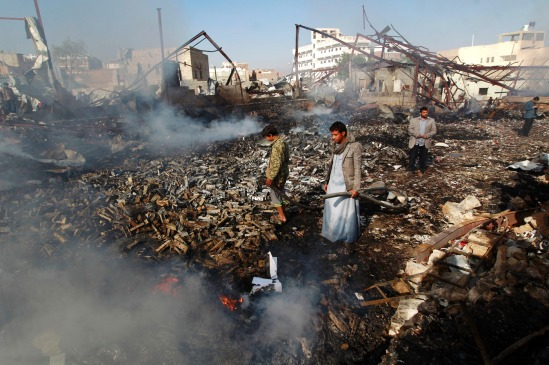 "Yemeni men inspect the damage at the site of a Saudi-led coalition air strike which hit a sewing workshop, in the capital Sanaa, on February 14, 2016. The factory owner, Faisal al-Musaabi, told AFP that ""Two employees, including a 14-year-old boy, were killed and 15 others wounded in the overnight air raid,"".   The coalition has been carrying out air strikes against Iran-backed rebels across Yemen since March.   / AFP / MOHAMMED HUWAIS        (Photo credit should read MOHAMMED HUWAIS/AFP/Getty Images)"