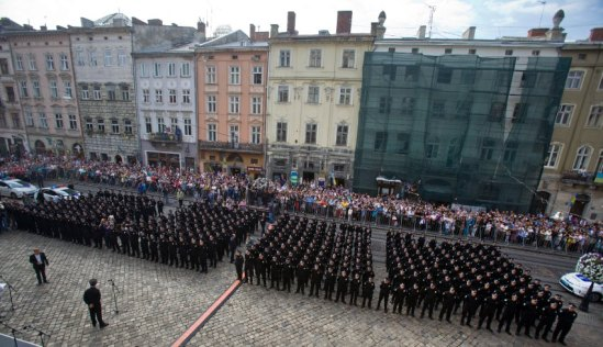 The new street patrol police officers attend oath rite during a ceremony in Lviv, Ukraine, Sunday, Aug. 23, 2015. 406 street patrol police officers took the oath rite and will start their patrol of the streets in Lviv. (AP Photo/Petro Zadorozhnyy)