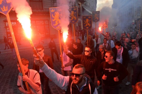 "Ukrainian ultra-nationalists burn flares and shout slogans as they march in the center of the western city of Lviv on April 28, 2016 to mark the 73rd anniversary of 14th SS-Volunteer Division ""Galician"" foundation.  The 14th Waffen Grenadier Division was a World War II German military formation initially made up of volunteers from the region of Galicia with a Ukrainian ethnic background, but later also incorporated Slovaks, Czechs and Dutch volunteers and officers.  / AFP PHOTO / Yuriy Dyachyshyn"