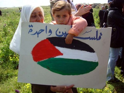 Palestinian_child_holds_a_sign_on_Land_Day-400x300